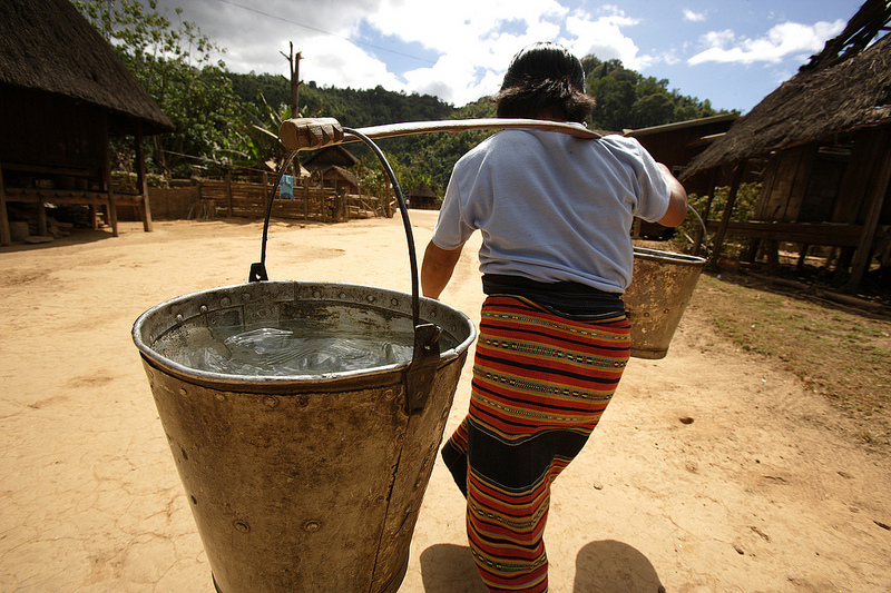 A woman carries heavy buckets of water back from a standpipe, Ban Chaling, Dakcheung, near Sekong, Laos. Source: DFAT photo library flickr's photostream, used under a creative commons license.
